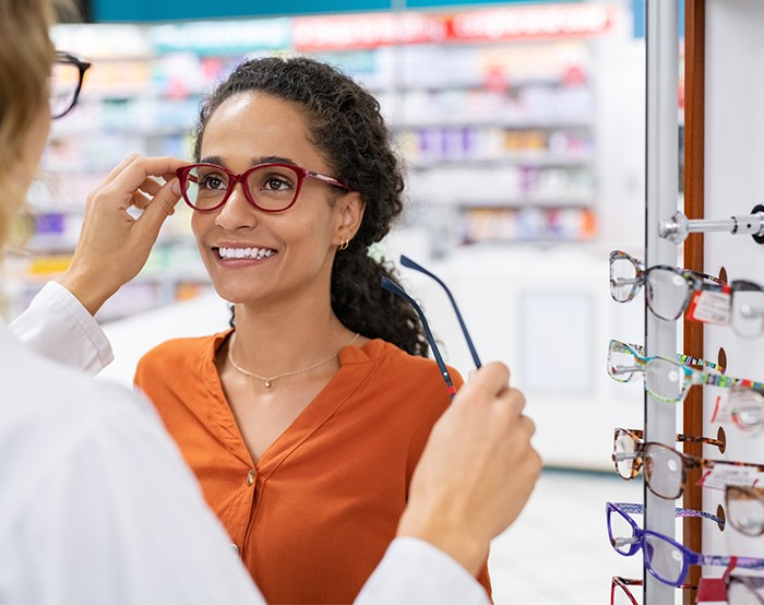 Eye doctor helping woman try on a variety of glasses to find the right pair